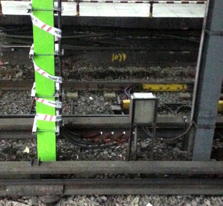 Nótese cómo la catenaria rígida colecta energía del tercer riel mediante cuatro cables.