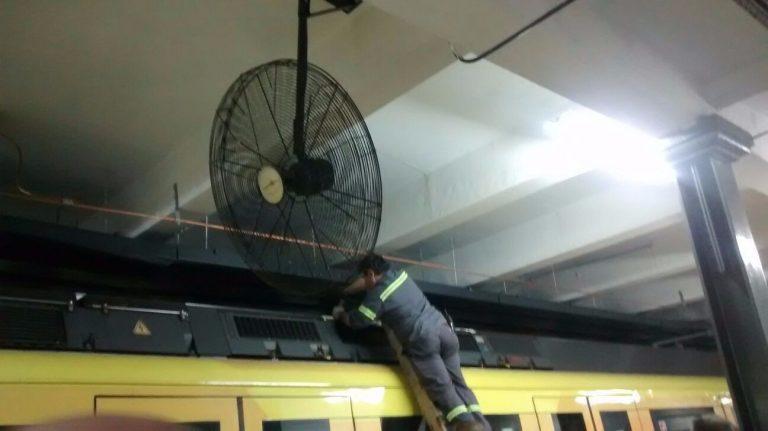 Personal despega la chapa del techo del tren de la catenaria rígida. Personal jerárquico supervisa la operación.