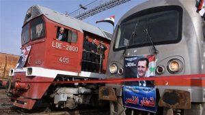Una lomotora y el DMU que realizó el recorrido, embanderados con fotos del presidente Al-Ásad.