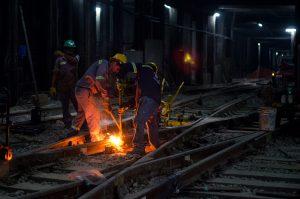 Operarios trabajan realizando una soldadura aluminotérmica.